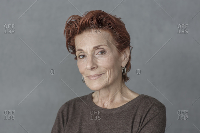 Head and shoulder portrait of beautiful mature woman with short red hair