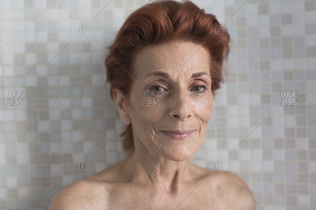 Bare shoulder portrait of smiling mature woman with short red hair