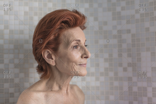Bare shoulder portrait of mature woman with short red hair