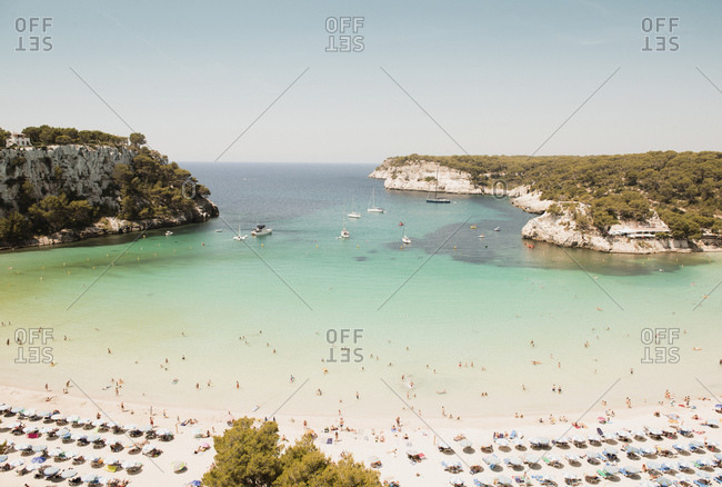 High angle view of tourists and rows of sunloungers on beach, Cala Galdana, Menorca, Balearic Islands, Spain