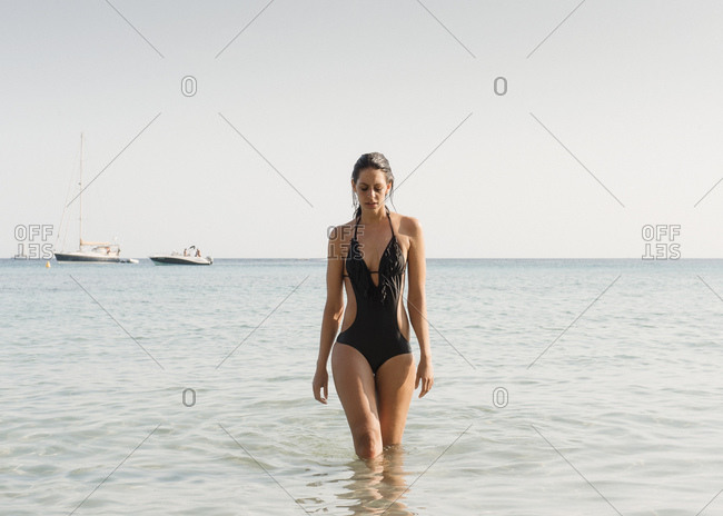 Young woman wearing bathing costume paddling in sea