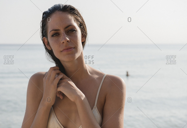 Portrait of beautiful young woman with wet hair at coast