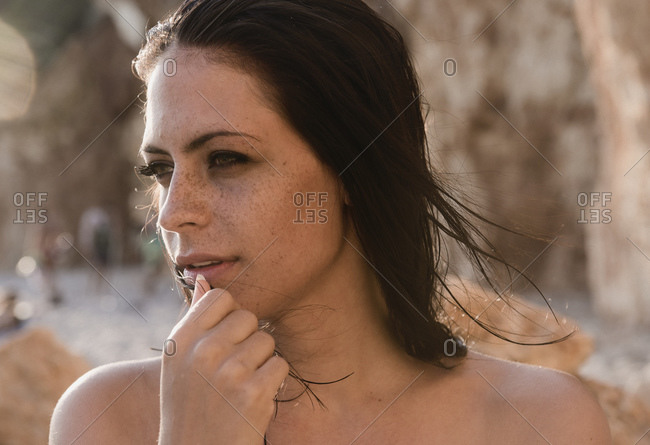 Portrait of beautiful bare shouldered young woman at beach