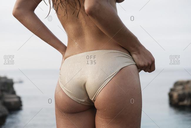 Cropped rear view of young woman wearing bikini bottoms at Cala en Brut, Menorca, Balearic islands, Spain