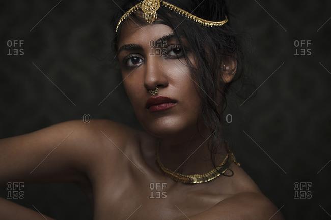 Low key portrait of beautiful young woman wearing gold headdress