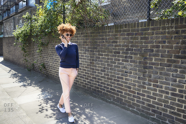 Young woman walking down street having telephone conversation on smartphone