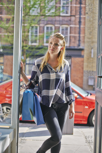 Mid adult woman holding shopping bags standing in doorway looking away