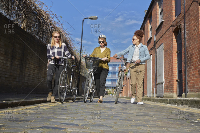 Low angle full length front  view of women pushing bicycles on cobblestone road