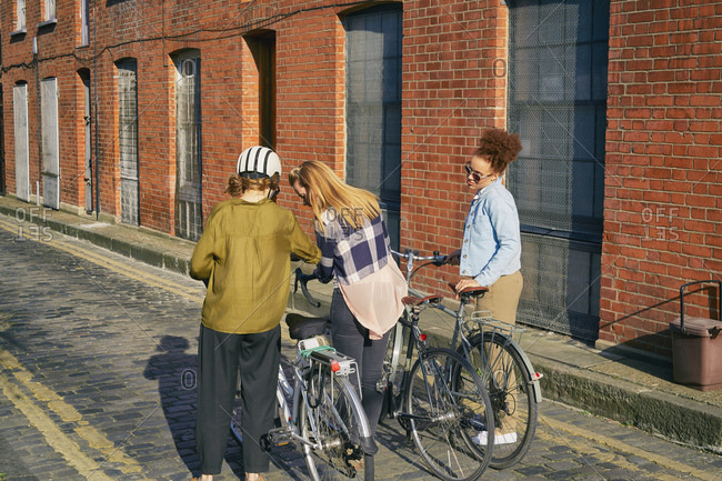 Rear view of women in urban area standing on cobblestone road holding bicycles