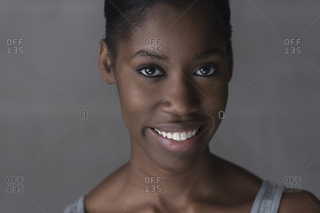 Portrait of young woman, smiling, studio shot
