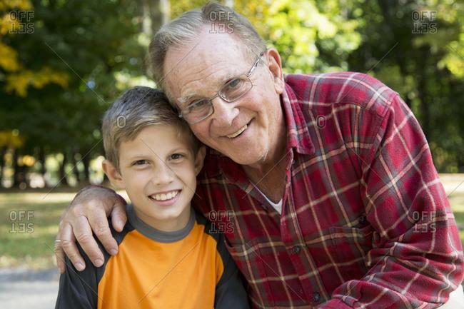 Portrait of senior man with arm around grandson in woods