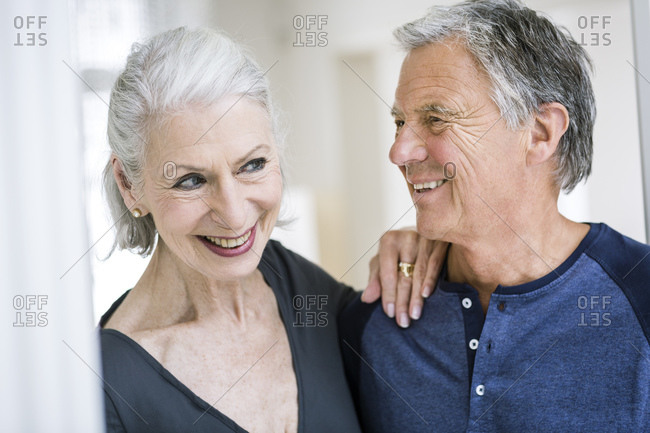 Senior woman with hand on senior mans shoulder smiling