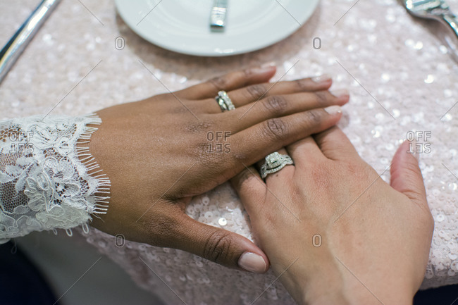 Bride couple's hands wearing wedding bands and engagement rings at wedding reception