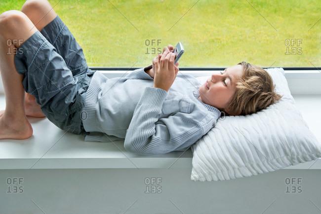 Boy lying on windowsill with mobile phone