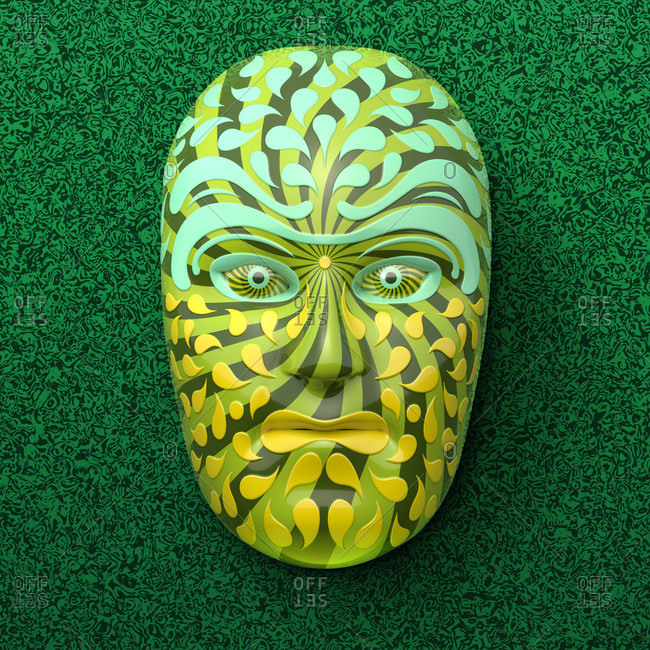 Asian theater mask with colored ornaments in green against a dark green marbled background
