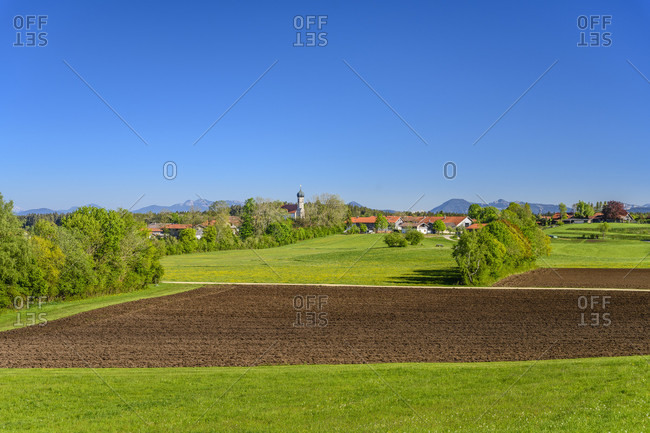 Germany, bavaria, upper bavaria, tiler land, dietramszell, lochen district, spring landscape and town view with church of st. magdalena against prealps