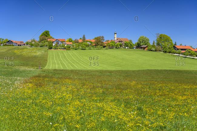 Germany, bavaria, upper bavaria, tiler land, eurasburg, berg district, spring landscape and town view with st. margaretha branch church