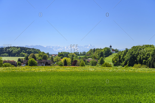 Germany, bavaria, upper bavaria, tiler land, munsing, holzhausen district, spring landscape and town view with parish church of st. johann baptist against wetterstein mountains with zugspitze