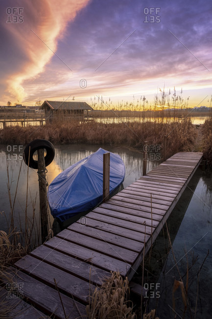 Jetty and boat on the lake shore at dawn