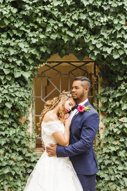 Wedding, newlyweds, young adults, diversity, portrait garden, window, hug