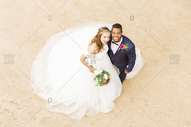 Wedding, newlyweds, young adults, diversity, love, sand, bird's eye view