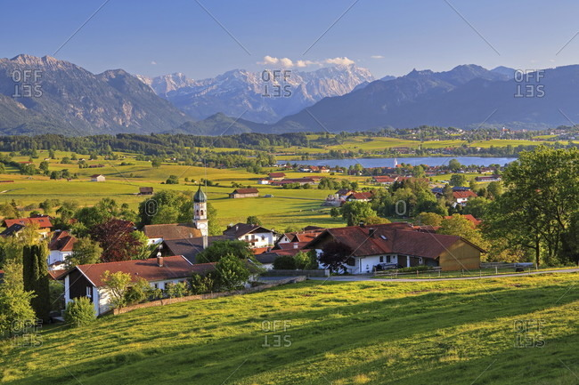 View of the village with riegsee, zugspitzgruppe (2962m) in the wetterstein mountains and ammergau alps, aidling, das blaue land, upper bavaria, bavaria, germany