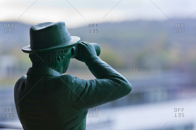 Man watching figurine with binoculars