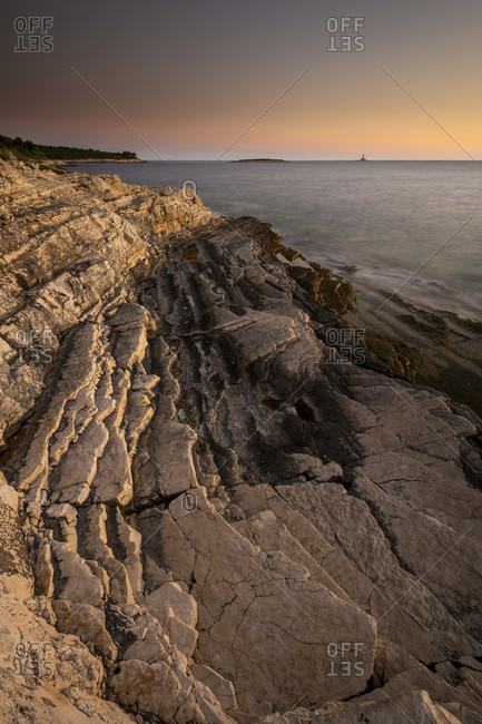 Evening light after sunset on the shores of the mediterranean sea on cape kamenjak in istria, croatia. rugged rocks, long exposure to smooth water and a small island in the background.