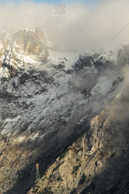 A support beam of the karwendelbahn, the mountain railway between mittenwald and the western karwendelspitze in the evening light with snow and clouds