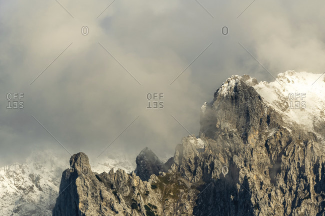 The viererspitze in the karwendel, in the background the warner with snow in the warm evening light with dramatic clouds