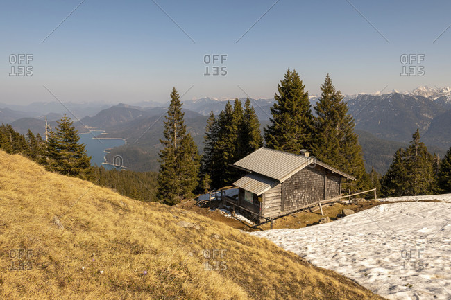 Mountain guard hut on the simetsberg with some old snow, in the background the karwendel and the walchensee
