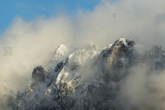The linderspitze with summit cross and snow between clouds with a blue sky above