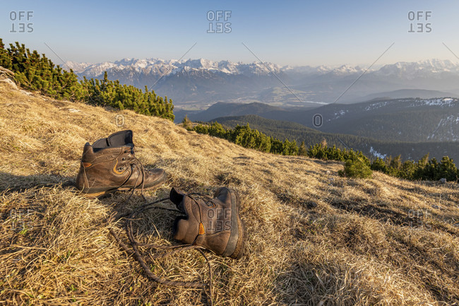 Leather hiking shoes in the warm light on the mountain slope, in the background the karwendel.