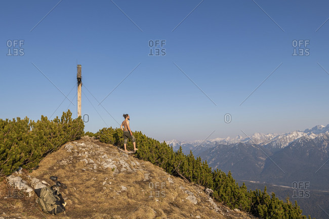 Mountaineers during the summit break on the simetsberg, enjoy the view of the karwendel mountains next to the summit cross