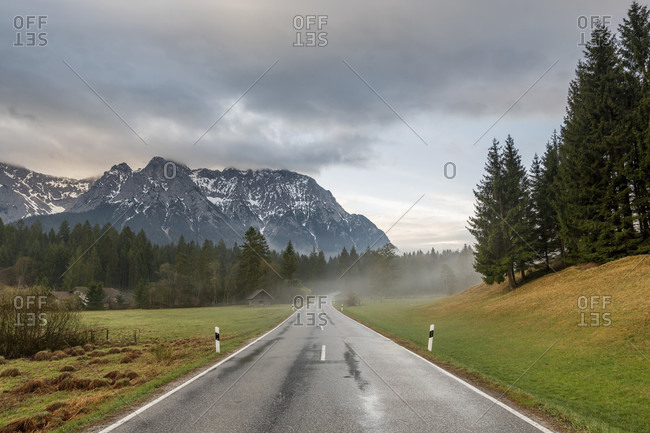 Early morning on the country road at schmalensee near mittenwald, the road is wet with rain, light fog rises and the karwendel towers in the background