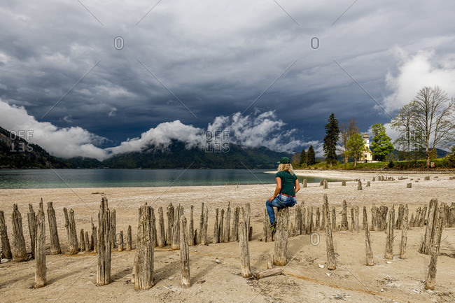 A young woman sits casually on old wooden planks on the banks of lake walchensee on the zwergern peninsula. in the background a dramatic mood of the weather and the small chapel st. margareth.