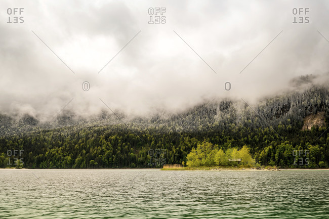 A small green island with a log cabin in the spring-like eibsee below the cloud-covered zugspitze. fresh snow lies on the forest in the background during the ice saints.