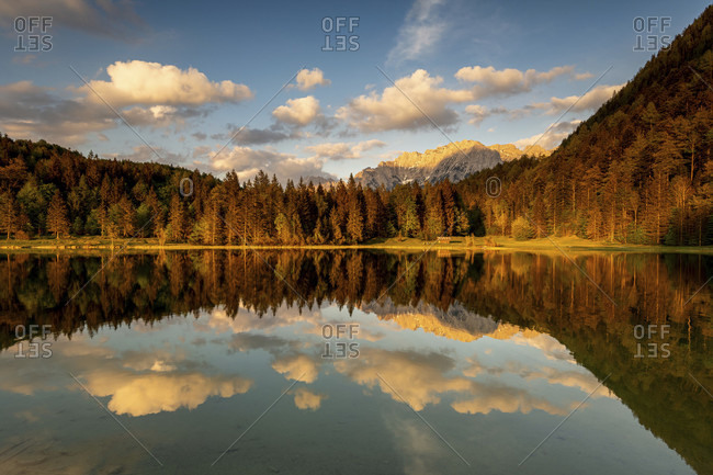 Evening light with light clouds at the ferchensee, above mittenwald. the edge of the forest and the karwendel in the background are warmly lit and reflected in the clear water of the lake.