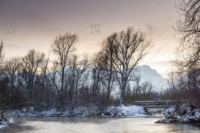 Evening mood on the loisach with a wooden bridge, water and fresh snow in winter. the zugspitze in the background