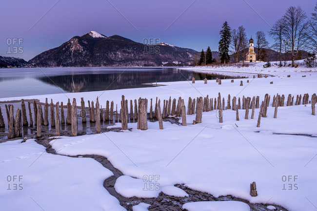 The small chapel of st. margareth, jochberg in the background and in the foreground the ancient wooden planks of a historic fish or crayfish farm on the banks of the walchensee in winter with snow, shortly after sunset in special colors