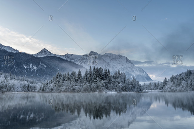 Sunrise at the winter reservoir krun after nightly fresh snow and in the background the karwendel mountains