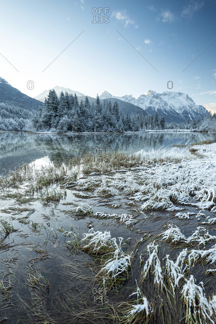 Blue hour before sunrise at the krun reservoir with light fog and blue sky. in the background a small island and the karwendel with snow and water reflection