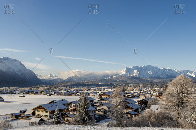 View of the snow-covered village of wallgau in the bavarian alps in winter with fresh snow and a blue sky