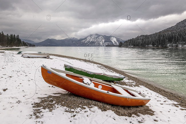 Onset of winter on the banks of the walchensee in the bavarian prealps. in the foreground a rowboat and in the background the Herzog stand with snow and dark clouds in spring.