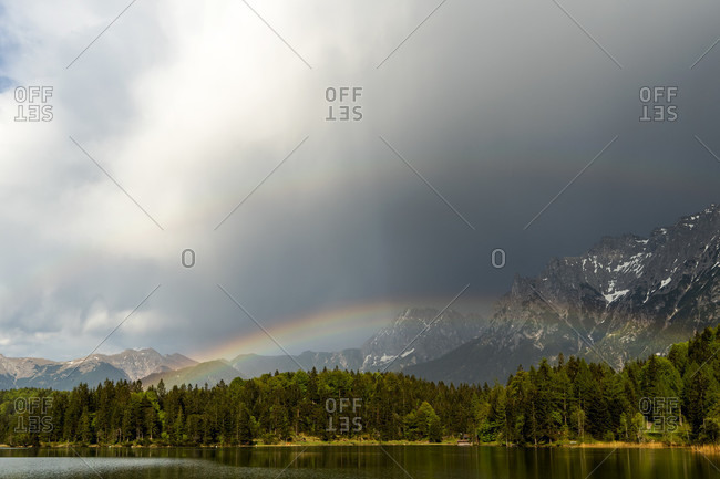Rainbow after storm at lautersee near mittenwald in the bavarian alps. in the background the clouds and the karwendel mountains