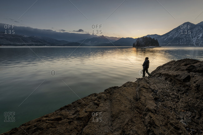 A lonely angler at nightfall on the banks of the walchensee on a rocky outcrop