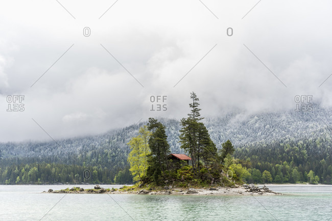 A small lonely island with a log cabin and red roof, in the middle of the beautiful eibsee below the zugspitze in the bavarian alps of the wetterstein mountains during the eisheiligenfresh snow in the background on the forest and cloud mood.