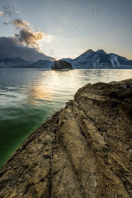 Evening mood with rock on the banks of the walchensee, in the background the island of sassau and the Herzog stand with a dark cloud front