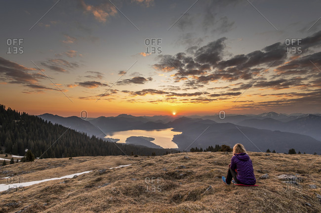 Trail runner katharina kirschner enjoys the view over the walchensee, the estergebirge and karwendel in the bavarian prealps during golden sunrise.