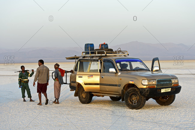 November 13, 2017: Local guide, driver and security guard stand next to a four-wheel drive vehicle of a local tourism company on the salt crust of the assale salt lake, hamedala, danakil valley, afar region, ethiopia